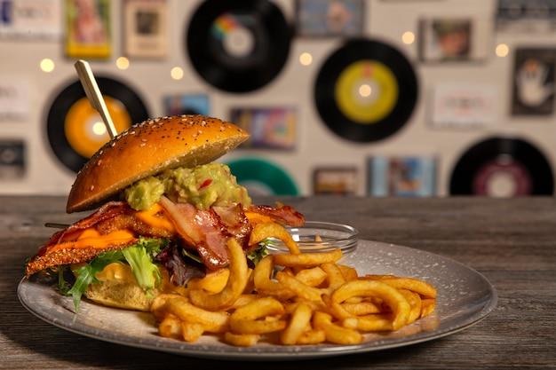 Domowy hamburger z chrupiącym kurczakiem, bekonem, guacamole z sosem i frytkami na drewnianym stole. odosobniony obraz.