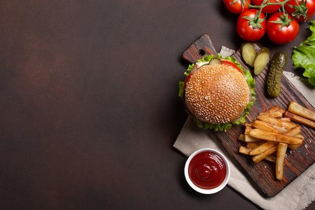 Domowy hamburger z dodatkami wołowiny, pomidorów, sałaty, sera, cebuli, ogórków i frytek
