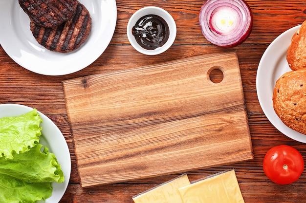 Domowy hamburger z kotletem, surówką, cebulą, pomidorem i serem