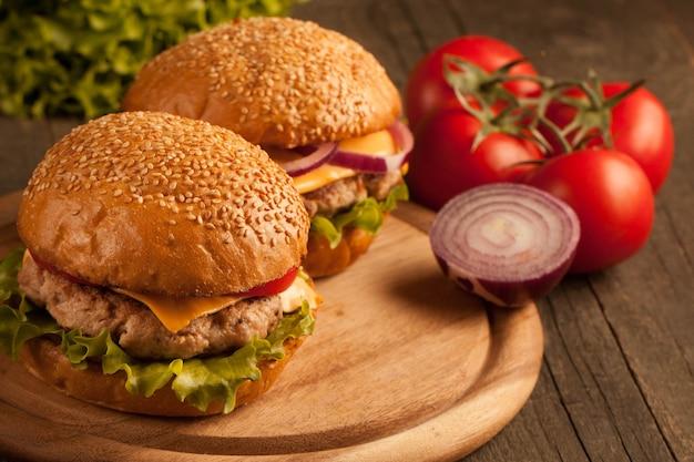 Domowy hamburger z wołowiną, cebulą, pomidorem, sałatą i serem. świeży burger z bliska na drewnianym stole rustykalnym z frytkami, piwem i frytkami. cheeseburger.