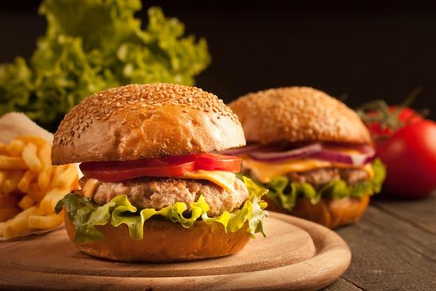 Domowy hamburger z wołowiną, cebulą, pomidorem, sałatą i serem.