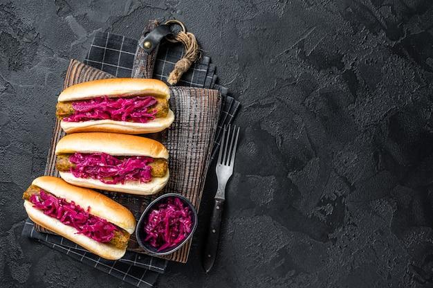 Domowy hot-dog wegański z bezmięsną kiełbasą wegetariańską i kapustą. czarne tło. widok z góry. skopiuj miejsce.