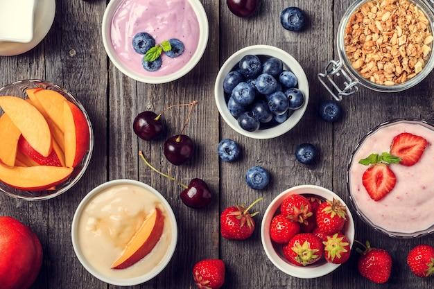 Domowy jogurt na tle drewnianych, widok z góry. zdrowa żywność, dieta, detoks, czyste odżywianie lub koncepcja wegetariańska.