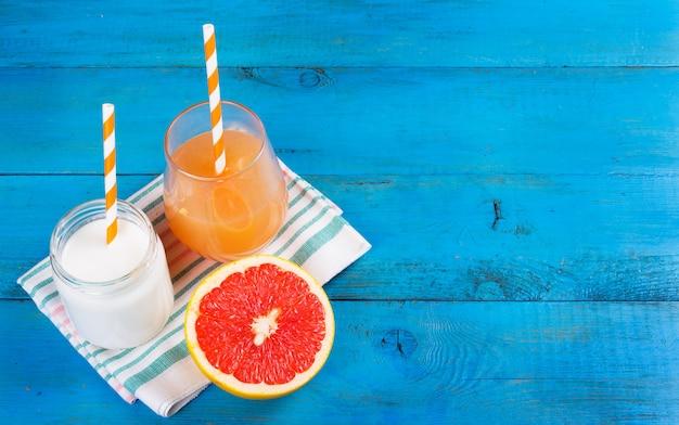 Domowy jogurt, sok i pół grejpfruta na niebieskim tle drewnianych.
