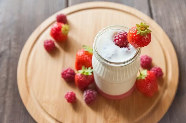 Domowy jogurt w słoju z bliska. fermentowany produkt mleczny z truskawkami i miejsca kopiowania.