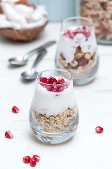 Domowy jogurt z granolą i owocami granatu w okularach na białym drewnianym stole. zdrowe śniadanie.
