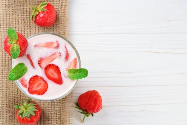 Domowy jogurt ze świeżą czerwoną truskawką na drewnianym tle. widok z góry.