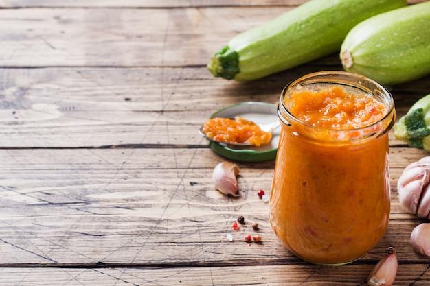 Domowy kawior z cukinii, pomidorów i cebuli w szklanym słoju na drewnianym. konserwy domowej produkcji, duszone warzywo w puszkach.