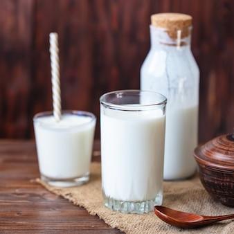 Domowy kefir, jogurt z probiotykami w szklance na stole probiotyczny zimny sfermentowany napój mleczny modne jedzenie i picie przestrzeń w stylu rustykalnym.