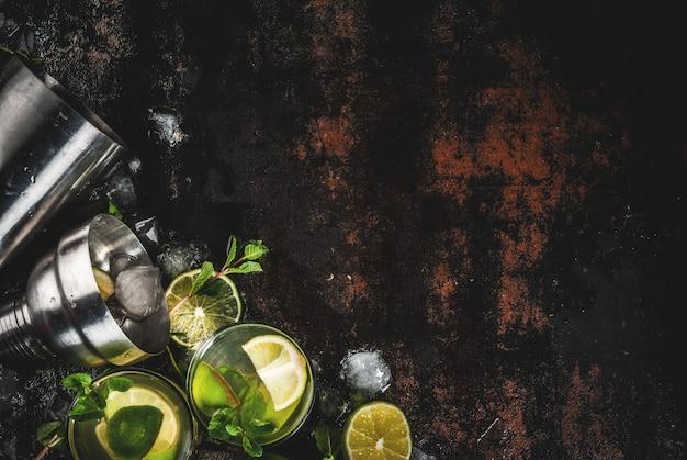 Domowy koktajl lemoniady lub mojito ze świeżymi liśćmi limonki i mięty, ciemny zardzewiały metal, widok z góry