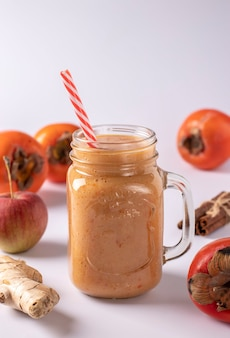 Domowy koktajl z persymony, jabłek, imbiru i cynamonu dla zwiększenia odporności w szkle na białej powierzchni,