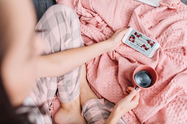 Domowy komfort na łóżku w nowoczesnym mieszkaniu ładnej kobiety oglądającej film na telefonie. widok z góry kobieta z filiżanką kawy ciesząc się domową harmonią, weekendy, dzień dobry na różowym kocu