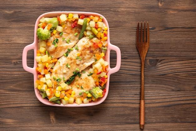 Domowy kurczak pieczony z różnymi przyprawami i warzywami na ciemnym tle drewnianych.