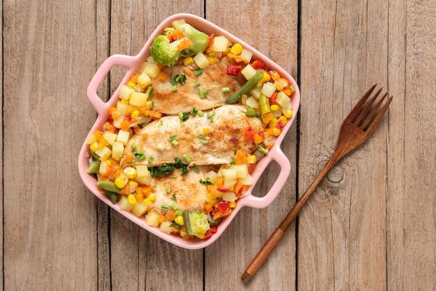 Domowy kurczak z grilla z różnymi pysznymi warzywami na jasnym tle drewniane. widok z góry.