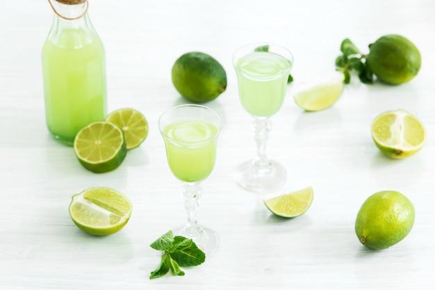 Domowy likier wapniowy w szklance i świeżych cytryn i limonek na białym tle