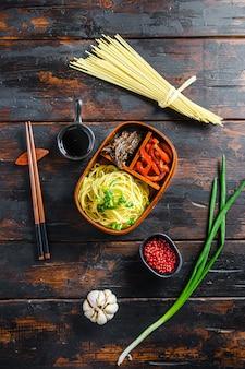 Domowy lunch w opakowaniu bento, grillowana wołowina i makaron ze składnikami widok z góry na rustykalne ciemne deski z drewna.