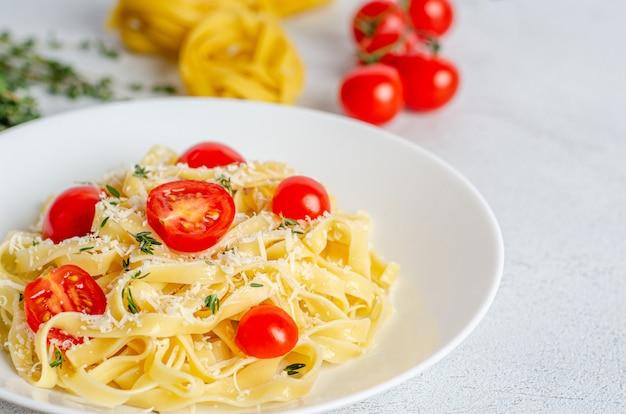 Domowy makaron fettuccine z pomidorami, tymiankiem, parmezanem w białym talerzu na jasnej powierzchni