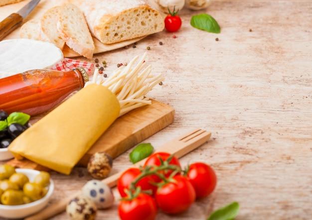 Domowy makaron spaghetti z jajkami przepiórczymi z butelką sosu pomidorowego i sera. klasyczne włoskie jedzenie na wsi. czosnek, pieczarki, czarne i zielone oliwki, chleb i szpatułka.
