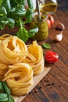 Domowy makaron tagliatelle w brązowym papierze na białym tle z oliwą z oliwek, sosem pesto, bazylią i czosnkiem
