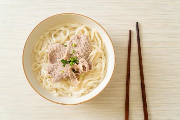 Domowy makaron udon ramen z wieprzowiną w klarownej zupie