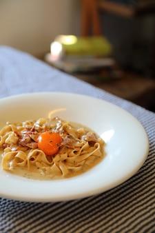 Domowy makaron z białym sosem, spaghetti carbonara, włoskie jedzenie