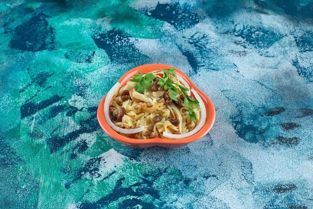 Domowy makaron z fasolą na misce, na niebieskim stole.