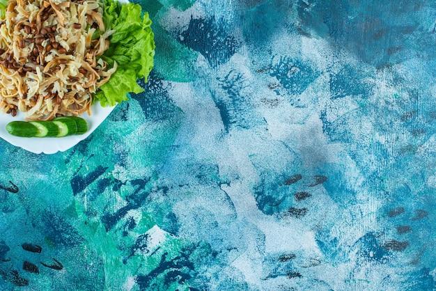 Domowy makaron z plasterkiem ogórka na talerzu, na niebieskim stole.