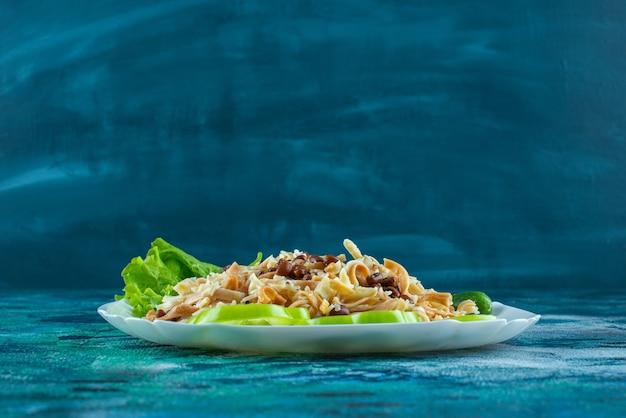 Domowy makaron z plasterkiem pieprzu na talerzu, na niebieskim stole.