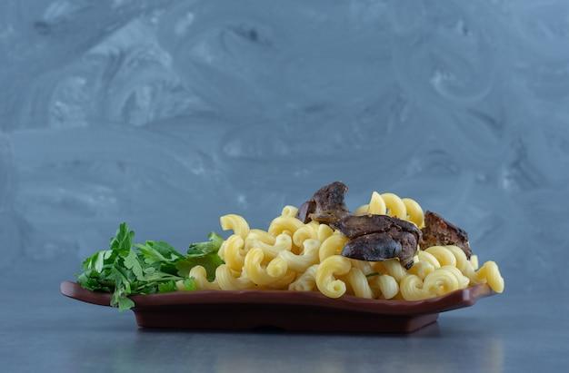 Domowy makaron z suszonym mięsem na brązowym talerzu.