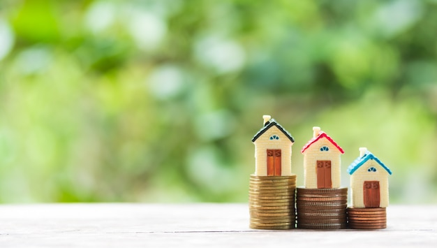 Domowy model i moneta pieniądze na stole dla pojęcia finanse i bankowości.