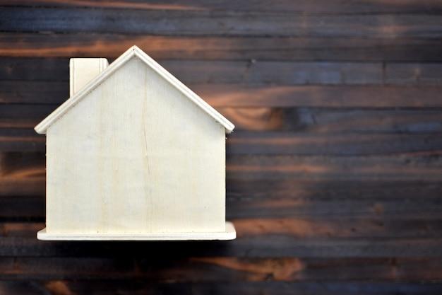 Domowy model na starym drewnianym tle, ratuje dla mieszkaniowego.