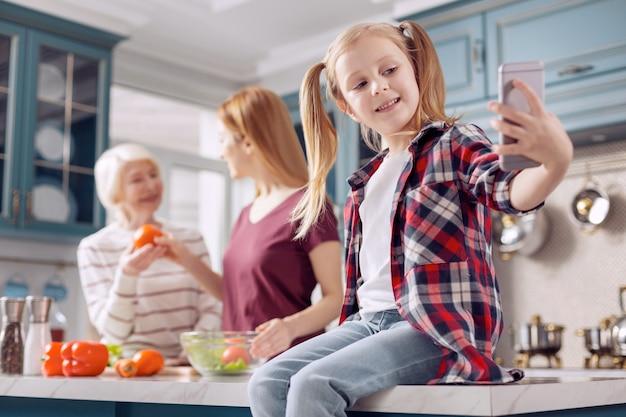 Domowy moment. urocza mała dziewczynka siedzi na kuchennym blacie i robi selfie, podczas gdy jej mama i babcia gotują sałatkę w tle
