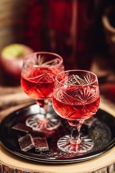 Domowy napój alkoholowy jagodowy i batony czekoladowe na metalowej tacy