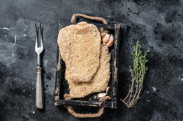 Domowy niemiecki wiener surowy sznycel w drewnianej tacy. czarne tło. widok z góry.