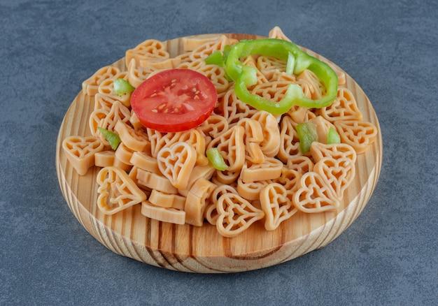 Domowy obiad z makaronem w kształcie serca i warzywami.