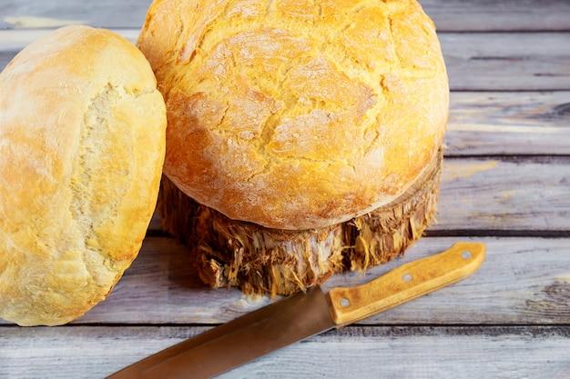 Domowy okrągły chleb żytni na podłoże drewniane z nożem.