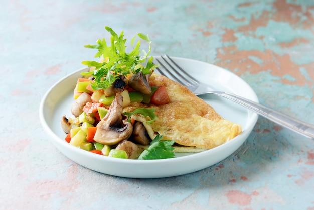 Domowy omlet z pieczarkami, warzywami i rukolą na talerzu. cudowne zdrowe śniadanie przy oknie z filiżanką kawy.