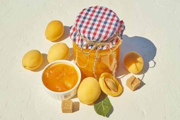 Domowy organiczny dżem morelowy i dojrzałe morele i brązowy cukier.