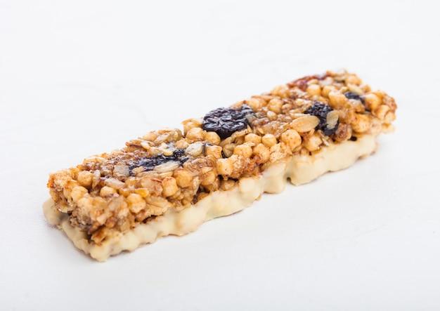 Domowy organiczny granola zboże bar z dokrętkami i suszonymi owoc na bielu.