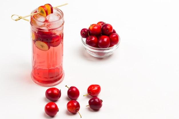 Domowy, orzeźwiający letni napój jabłkowy z lodem w szkle. pokrojone jabłka na patyku. małe czerwone jabłka na stole iw szklanej filiżance. białe tło. widok z góry.