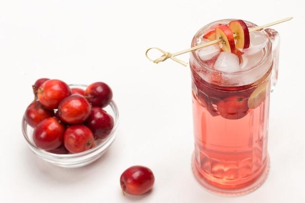 Domowy, orzeźwiający letni napój jabłkowy z lodem w szkle. pokrojone jabłka na patyku.