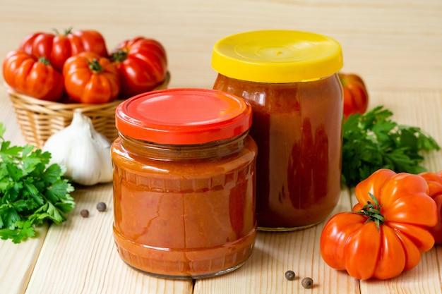 Domowy ostry sos pomidorowy z czosnkiem i papryką w szklanych słoikach na drewnianym stole.
