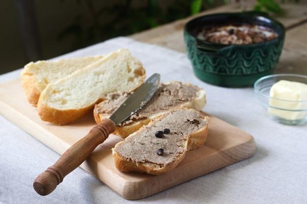 Domowy pasztet z wątroby z chlebem i masłem. styl rustykalny.