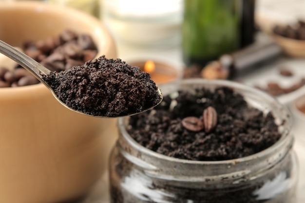 Domowy peeling kawowy do twarzy i ciała w zbliżeniu łyżką na jasnym tle. kosmetyki pielęgnacyjne.