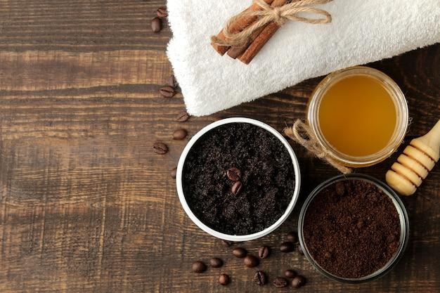 Domowy peeling kawowy w białym słoiczku do twarzy i ciała oraz różne składniki do wykonania peelingu. spa. kosmetyki. kosmetyki pielęgnacyjne. widok z góry z miejscem na tekst