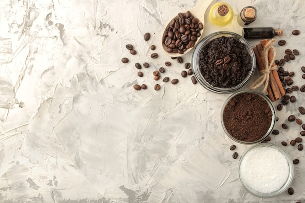 Domowy peeling kawowy w słoiczku do twarzy i ciała oraz różne składniki do wykonania peelingu na jasnym tle. spa. kosmetyki. kosmetyki pielęgnacyjne. widok z góry z miejscem na tekst