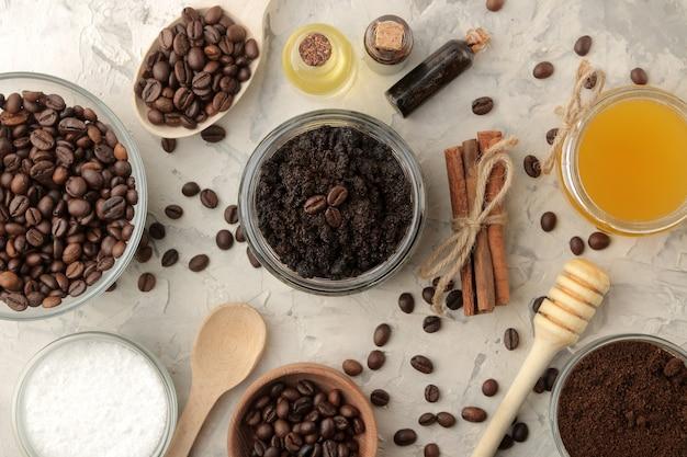 Domowy peeling kawowy w słoiczku do twarzy i ciała oraz różne składniki do wykonania peelingu na jasnym tle. spa. kosmetyki. kosmetyki pielęgnacyjne. widok z góry