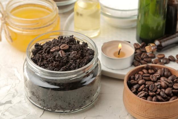 Domowy peeling kawowy w słoiczku do twarzy i ciała oraz różne składniki do wykonania peelingu na jasnym tle. spa. kosmetyki. kosmetyki pielęgnacyjne.