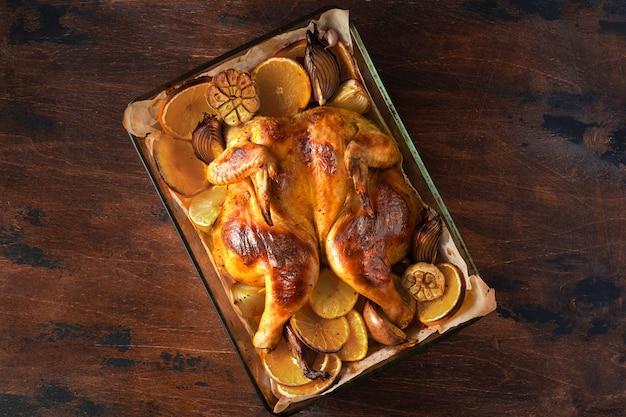 Domowy pieczony kurczak z cytryną, czosnkiem i pomarańczami na rustykalnym drewnie