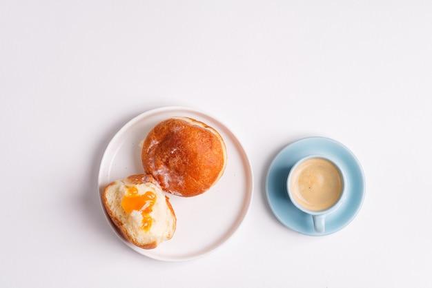 Domowy pieczony pączek na białym talerzu ceramicznym i filiżanka kawy na jasnoszarym tle. leżał płasko.